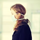 stock photo of swine flu  - Woman wearing a mask to prevent flu infection - JPG