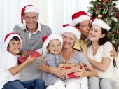 image of christmas party  - Family in sofa giving presents for Christmas - JPG