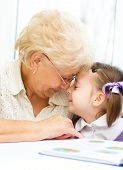 stock photo of granddaughter  - Grandmother teaches to read a book her granddaughter