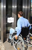 stock photo of physically handicapped  - A Wheelchair user on defect elevator door - JPG