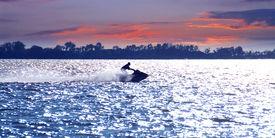 stock photo of waverunner  - Man on jet ski at sunset - JPG