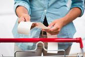 image of receipt  - Unrecognizable woman in light blue shirt checking a long grocery receipt at store.