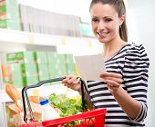 picture of supermarket  - Woman at supermarket holding a full shopping basket and a shopping list - JPG