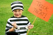picture of halloween  - A young American child is dressed up in a prisoner costume on Halloween getting ready to go trick - JPG