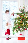 stock photo of girl next door  - Adorable toddler girl with curly hair wearing a warm red dress helping her brother to decorate a beautiful Christmas tree standing next to a big window with a view of a snowy garden - JPG