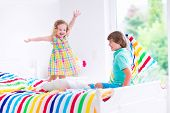 foto of pillow-fight  - Two children happy laughing boy and cute curly little girl having fun at pillow fight with feathers in the air jumping laughing and giggling in a white bedroom with colorful bedding - JPG