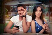 picture of diners  - Young adult couple has privacy problems with modern technology - JPG