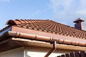 stock photo of red roof tile  - Red roof tile with chimney and cloudy sky on background - JPG
