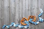 pic of pretzels  - Bavarian pretzels with ribbon on wooden board as a background for Oktoberfest - JPG