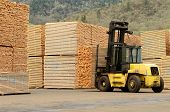 stock photo of lift truck  - Large lift truck moving a stack of green fir 2 x 4 lumber studs at a small log processing mill in southern Oregon ready for the drying kiln