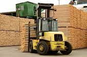 stock photo of 2x4  - Large lift truck moving a stack of green fir 2 x 4 lumber studs at a small log processing mill in southern Oregon ready for the drying kiln