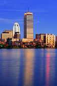 stock photo of prudential center  - Boston city skyline at dusk with Prudential Tower and urban skyscrapers over Charles River with lights and reflections - JPG