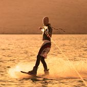 pic of watersports  - Wakeboarder in colorful shorts riding in sunset.