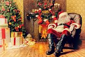 Santa Claus brought gifts for Christmas and having a rest by the fireplace. Home decoration. poster