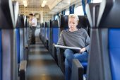 stock photo of passenger train  - Young woman traveling by train - JPG