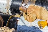 image of pipe-welding  - Welder is welding a pipe in a trench - JPG