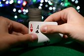 stock photo of poker hand  - Chips and cards for poker in hands on green table - JPG