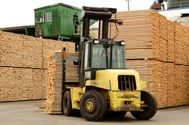 stock photo of logging truck  - Large lift truck moving a stack of green fir 2 x 4 lumber studs at a small log processing mill in southern Oregon ready for the drying kiln  - JPG