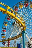 foto of riding-crop  - Close up ferris wheel and roller coaster track - JPG