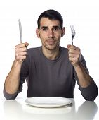 stock photo of knife  - Man at dinner table with fork and knife raised - JPG