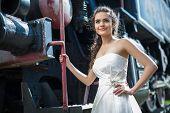 foto of locomotive  - Portrait of happy wedding bride near the old steam locomotive - JPG