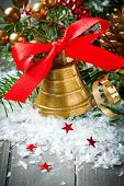 image of christmas bells  - Christmas composition with golden bell with red satin ribbon bow and branch of christmas tree - JPG
