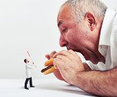 pic of junk  - close up photo of man eating burger and small doctor looking at him and protesting against junk food - JPG