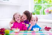 picture of child feeding  - Family having breakfast in a white sunny kitchen - JPG