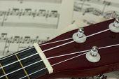 stock photo of ukulele  - Close up of a ukulele rested on sheet music  - JPG