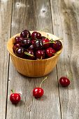 image of black-cherry  - Close up image of freshly picked whole black cherries in bowl on rustic wooden table - JPG