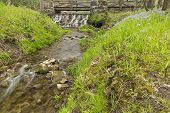 foto of dam  - A dam under a footbridge with a creek during spring - JPG