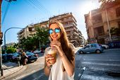 image of walking away  - Young woman walking on the street with take away coffee  in the transparent cup in the city - JPG