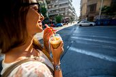 stock photo of walking away  - Young woman walking on the street with take away coffee  in the transparent cup in the city - JPG