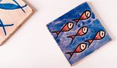 picture of tile  - blue tile with a group of five red fishes drawing on it and a piece of a second tile on the left corner - JPG