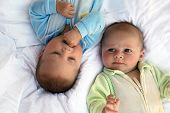 stock photo of twin baby  - two baby boys twin brothers lying on a bed - JPG