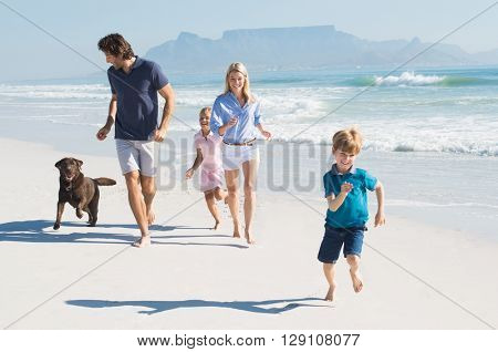 Family playing with pet on the beach. Happy beautiful family running at beach with pet dog. Smiling