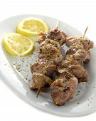 stock photo of souvlaki  - Two greek souvlaki or kalamaki in a plate with lemons isolated on white background - JPG