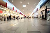 foto of shopping center  - Wide hall and buyers in trading center with shops on both sides - JPG