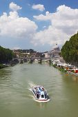 Boat on Tiber river, Sant' Angelo Bridge and Basilica of St. Peter in Rome, Italy