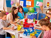 Постер, плакат: Children with teacher woman painting on paper at table in kindergarten Children learn painting i
