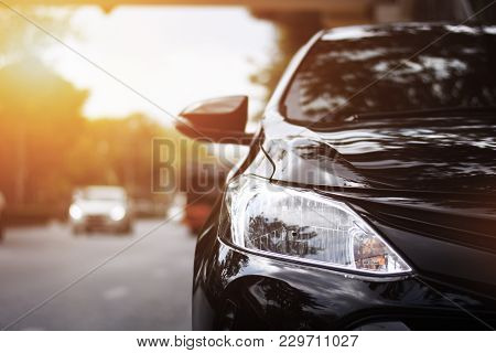 poster of Focusing On The Black Car Headlights On A Street Corner With Sunlight Flares, In The Background, The