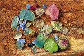 stock photo of precious stone  - Precious stones like aquamarine tourmaline peridot and saphire on a wooden backgrond - JPG
