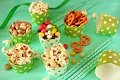 Popcorn, Multicoloured Drops, Pretzels With Salt And Pistachio Nuts In Paper Cups On Green Backgroun poster