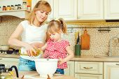 Young Mother And Cute Little Daughter Preparing The Dough, Bake Cookies And Having Fun In The Kitche poster