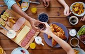 food, eating and family concept - group of people sharing jam for breakfast at wooden table poster