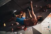 Man Bouldering At An Indoor Climbing Centre While A Woman Looks On. Climber Practicing Rock Climbing poster
