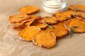 Parchment with tasty sweet potato chips on table, closeup poster