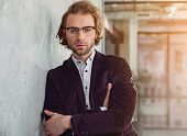 Confident Unshaven Smart Male Leaning Against Wall While Standing In Apartment. Self-confidence Conc poster