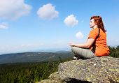 picture of witch-doctor  - Young woman meditating on a high peak - JPG