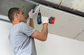 Construction Worker Assemble A Suspended Ceiling With Drywall And Fixing The Drywall To The Ceiling  poster